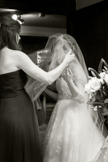 Bridemaid helps with veil at Church Door