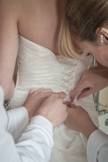 Bridesmaids help with the Bride's dress
