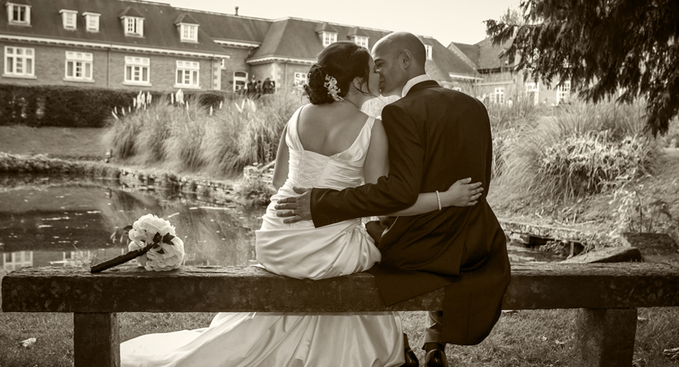 Bride and Groom kiss down by the lake at Albrighton Hall